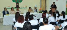imagem de mulheres sentadas em cadeiras, ângulo por trás. à sua frente, professores e professoras do curso sentados numa mesa. enquanto um homem fala ao microfone num púlpito
