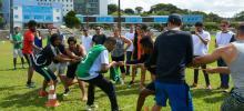 Estudantes do curso de educação física disputando cabo de guerra. Ao fundo, fachada da UFRPE