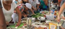 Participante da aula prática, ao redor de uma mesa, com vários legumes e frutas, fazendo receitas gastronômicas