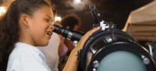 menina observando a lua em telescópio