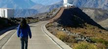 imagem da aluna Inês de costas caminhando rumo ao telescópio Soar no Chile