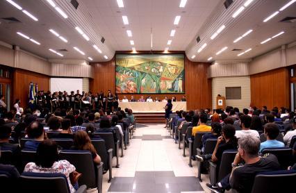 Imagem do Salão Nobre da UFRPE durante aula inaugural. Estudantes sentados e mesa das autoridades ao fundo